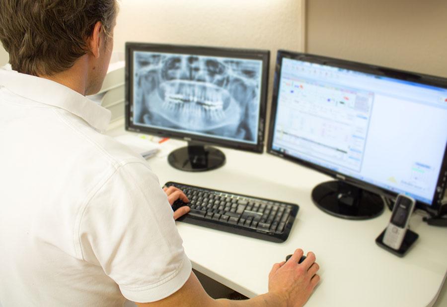 Zahnarzt Dr Krautz schaut auf Roentgenbild